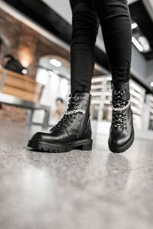 Seasonal fashion collection of women's boots. Stylish young woman in fashionable spring-autumn black leather lace-up shoes in trendy jeans walks on the store. Shopping. Close-up. Banque d'images - 135486884