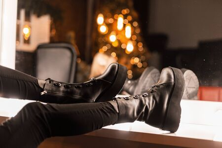 Stylish youth leather black boots on female legs. Closeup of female legs in jeans in fashionable shoes near a vintage mirror with bright lamps. Girl chooses footwear for a party. Banque d'images - 135486903