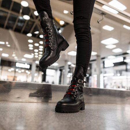 Young woman in a fashionable black leather boots with red shoelaces in vintage jeans poses in a store. Close up of female legs in stylish seasonal shoes. Autumn-winter footwear. New collection. Banque d'images - 135486786