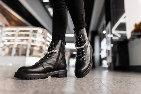 Young trendy woman in black stylish jeans in fashionable leather lace-up boots stands the mall. Fashion collection of womens autumn shoes with shiny rhinestones. Close-up of female legs in footwear.