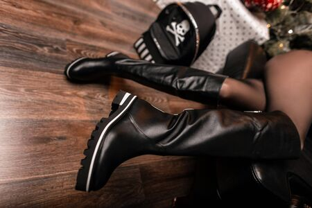Fashionable women's black leather boots close-up with a stylish leather backpack with a skull pattern in the room. New youth collection of shoes and trendy accessories. Close-up. Reklamní fotografie