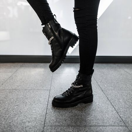 Young modern woman in black stylish jeans in fashionable leather lace-up boots stands in a store. Trendy collection of womens autumn shoes with rhinestones. Close up of female legs in footwear. Reklamní fotografie