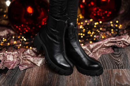 Christmas sale footwear. Winter collection of womens warm leather shoes. Closeup of female legs in black trendy boots near beautiful mirror balls.