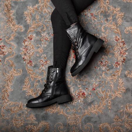 Close-up of female legs in vintage jeans in stylish brutal leather lace-up boots. Top view on a young woman in trendy shoes in a store. Fashionable winter-autumn new collection womens footwear. Banque d'images - 135486944