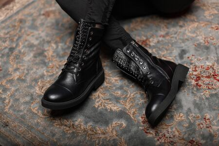 Fashionable young woman is sitting on a vintage floor in a store in black stylish leather shoes with lacing in jeans. Close up of female legs in trendy autumn spring boots. New stylish shoe collection Banque d'images - 135486800
