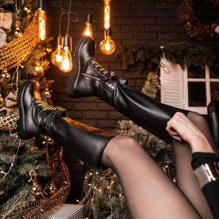 Fashionable black leather shoes with yellow shoelaces on female legs in the air on the background of the Christmas tree and vintage lamps. Trendy collection of seasonal womens shoes. Close-up.