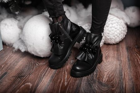 Stylish beautiful black leather winter boots on female legs near white vintage toys. New Years sale. Fashionable winter womens shoes. Close-up. Reklamní fotografie
