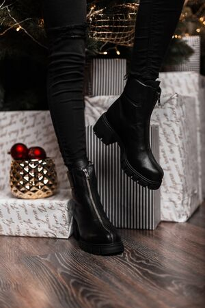 Fashionable leather black women's winter boots. Young woman in jeans in stylish shoes stands in a room near the holiday boxes and mirror balls. New Year's shopping. New seasonal shoe collection. Banque d'images - 135486912