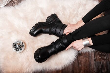 Trendy young woman sits on a soft white carpet in a store and measures fashionable winter leather warm boots. Stylish womens shoes with mirror ball. New Years shopping. View from above.