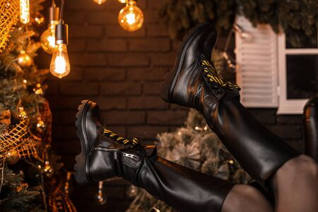 Trendy black leather winter boots on the background of New Years decorations in the room. New stylish seasonal collection of warm womens shoes. Youth style. Details of the everyday look.