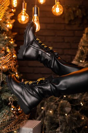 Womens leather black fashion lace-up boots. Woman sits in a room with a New Year tree with vintage bright lamps in stylish winter shoes. Close up of female legs in a trendy footwear.