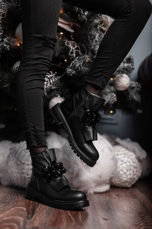 Trendy young woman in vintage jeans in fashionable leather black shoes poses near a Christmas tree in the room. Closeup of female legs in stylish boots. Winter fashion youth footwear. Banque d'images - 135487476