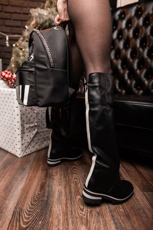 Close-up of female legs in fashionable black leather boots with trendy youth backpack with a skull pattern in the room. Stylish womens shoes and accessories.