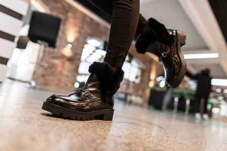 Young modern woman walks around the mall in leather fashionable black warm winter boots with fur in vintage jeans. Close up of female legs in stylish shoes. New seasonal collection.