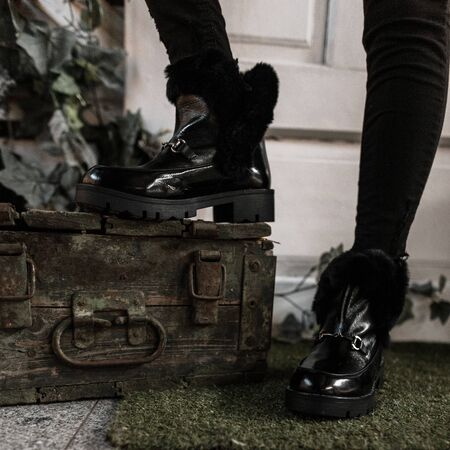 Youth fashionable black warm boots close-up. Young trendy woman in winter stylish shoes with fur stands near old chest in the room. Modern style.