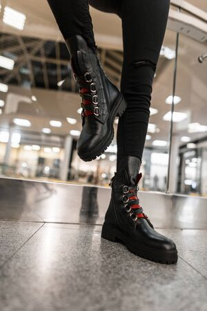 Close up of female legs in black jeans in fashionable black leather boots with red shoelaces in the mall. Stylish young woman posing in trendy footwear in the room. Youth womens shoes. Autumn fashion. Banque d'images - 135489154