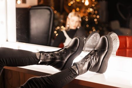 Young woman is going to a party. Close up of female legs in trendy black leather boots with thick sole near a vintage mirror with bright lamps indoors. Stylish new collection of womens winter shoes.