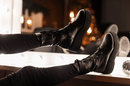 Fashionable young woman in stylish black warm leather shoes in trendy jeans near a vintage mirror with bright light bulbs in the room. Girl is going to a party. Close-up of female legs in shoes. Reklamní fotografie