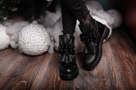 Beautiful fashionable black leather shoes on female legs indoors. Young trendy woman in stylish seasonal boots stands in a room near white vintage balls. New Year's shopping. New collection of shoe. Banque d'images - 135489132