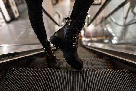 Close up of female fashionable leather black shoes with red shoelaces. Stylish seasonal boots. Youth new collection of autumn-winter womens footwear.