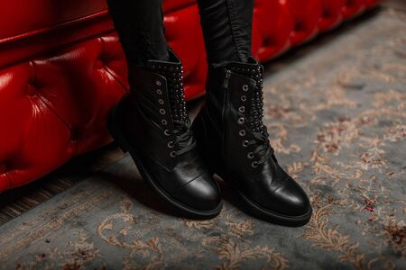 Stylish young woman is sitting in a shop on a red sofa in black fashionable leather shoes with lacing in vintage jeans. Close up of female legs in trendy autumn-spring boots. New seasonal collection. Reklamní fotografie