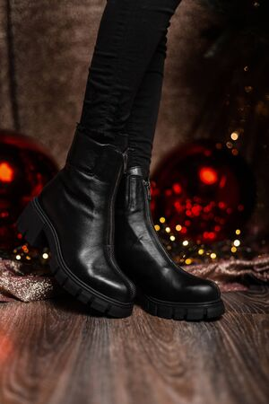 Youth trendy leather black womens winter boots. Young woman in jeans in fashionable shoes is standing in a room near shiny mirror balls. Christmas shopping. New seasonal shoe collection.
