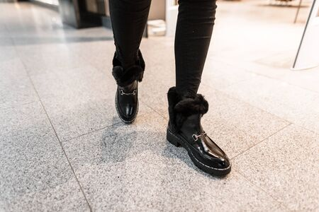 Fashionable young woman in warm leather winter boots with fur in vintage jeans walk on the store. Close-up of female legs in stylish shoes. New youth trendy collection womens footwear. Banque d'images - 135489323