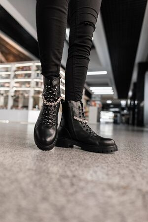 Closeup of female legs in fashionable leather black boots in vintage jeans in a store. Details of everyday look. Fashion autumn-winter. Banque d'images - 135489279