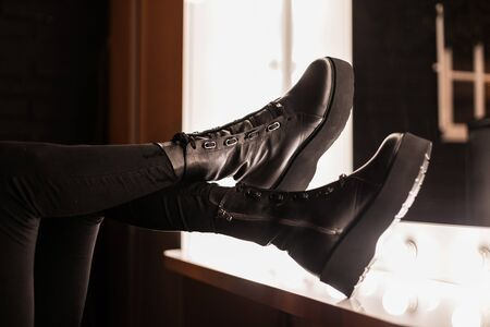 Trendy winter-autumn collection of women's shoes. Close-up of female legs in stylish black jeans in fashionable black leather boots near a vintage mirror with bright bulbs. Youth footwear. Banque d'images - 135489506