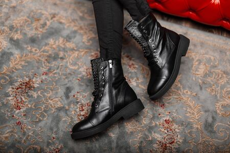 Fashionable seasonal leather black lace-up boots close-up. Stylish young woman is sitting on a red sofa in trendy shoes in vintage jeans indoors. New collection autumn-winter. Casual style. Banque d'images - 135489261