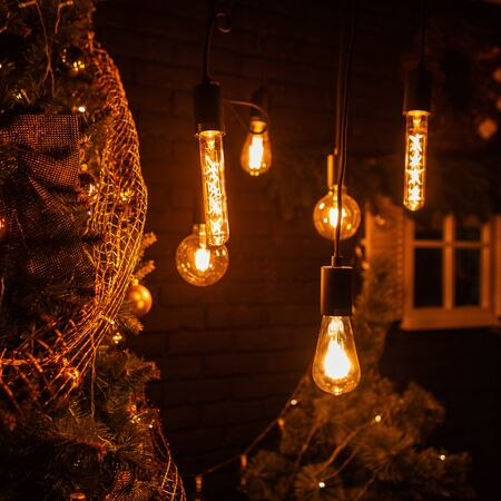 Beautiful dark room with old lamps with yellow light and a Christmas tree with golden toys and vintage garlands. Preparing for the winter holidays. Happy new year. Imagens