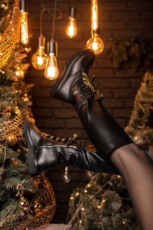 Close-up of female legs in leather fashionable black boots on the background of New Year's decorations in the studio. New collection of fashionable winter shoes. Christmas sale womens footwear. Foto de archivo