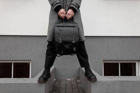 Primer plano de un hombre con un elegante abrigo a cuadros gris con pantalones elegantes en botas negras de invierno con una mochila de cuero en las manos cerca de una pared vintage en la ciudad. Nueva colección de moda de ropa masculina de temporada