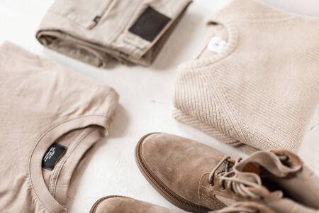 Botas elegantes de gamuza para hombres con suéteres casuales beige de moda con pantalones clásicos en un piso blanco. Colección de primavera de moda en colores pastel para hombre. Moda juvenil moderna. Estilo retro. De cerca.