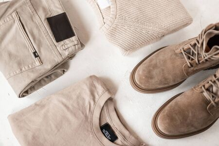 Modern fashionable mens autumn-spring beige suede boots with a stylish knitted sweater on a white table. Trendy classic look in a pastel colors for men. Elegant seasonal menswear and shoes. Top view.