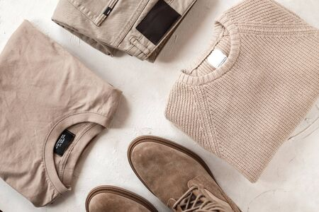 Group of fashionable clothes on the table. Beige denim pants, cotton shirt, woolen knitted vintage sweater and beige suede leather boots lie on the white floor. Classic elegant menswear. Top view.