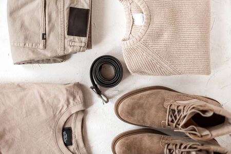 Black stylish leather belt lies next to a knitted sweater with classic trousers with suede boots with a cotton pullover on a white table. View from above. Fashionable mens clothing in beige colors.