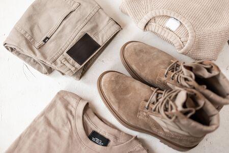 Conjunto de zapatos y ropa elegante para hombres en colores beiges sobre la mesa. Ropa de hombre de moda primavera-otoño. Detalles de moda masculina de look casual. De cerca.