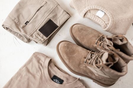 Set of men's stylish clothes and shoes in beige colors on the table. Fashionable men's spring-autumn clothes. Details trendy casual look menswear. Close-up.