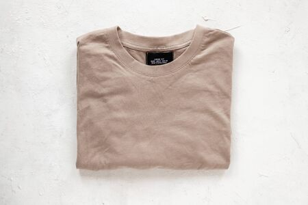 Top view on a stylish beige cotton pullover on the white background. Fashionable casual mens clothing. Trendy youth sweaters for men. Details of the everyday look. Close-up.