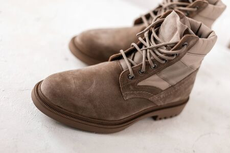 Men's beige suede boots with shoelaces on a white background in studio. Close-up of men's seasonal luxury shoes. Details. New winter collection footwear. Standard-Bild
