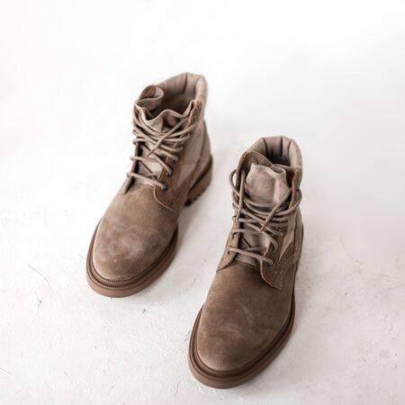 Fashionable men's beige spring shoes made of suede on a white background. Stylish seasonal collection of trendy shoes for men. Retro style. Close-up. View from above.