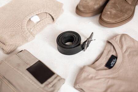Stylish black leather belt with a metal buckle lies on the table next to fashionable boots with a sweater with a pullover and trousers. Fashion classic look in pastel colors for men. View from above.