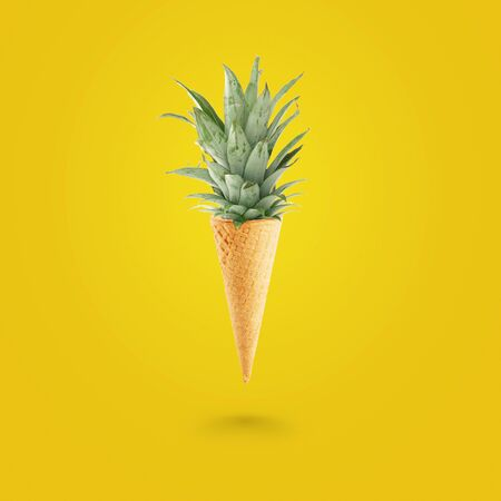 Summer concept, Ice cream cone with pineapple leaves on bright yellow background. Healthy food