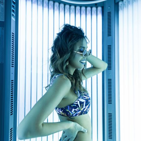 Stylish happy hipster girl with slim body and neon light. Funny young woman model with cute smile in a trendy blue swimsuit in vintage sunglasses with curly hair is posing and smiling in the solarium