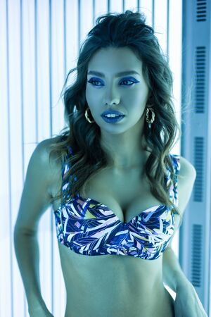 Sexy sensual young woman with curls with health tanned skin with blue lips in a stylish swimsuit is standing in a solarium with modern ultraviolet lamps. Elegant girl and neon light in a tanning bed. Reklamní fotografie