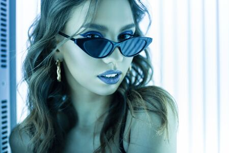Portrait of a European beautiful young woman in fashion sunglasses with sexy lips with curly hair with golden earrings in a solarium. Stylish cute glamorous girl model sunbathes under the ultraviolet. Standard-Bild