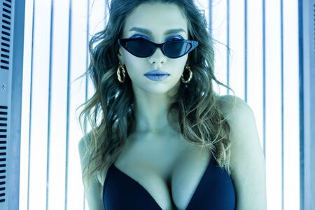 Portrait of a stylish young woman with sexy breasts with beautiful lips in sunglasses in a black bathing suit on a background of ultraviolet modern lamps. Glamorous cute girl sunbathes in a solarium.