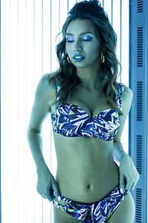 Glamorous young beautiful woman with a sexy healthy body in a blue stylish bikini with curly hair with chic make-up is standing in the solarium spa. Cute girl sunbathes and enjoys the neon light.