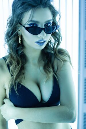 Portrait of a fashion young woman with sexy breasts with beautiful lips in sunglasses in a black bathing suit on a background of ultraviolet neon lamps. Glamorous elegant girl sunbathes in a solarium.